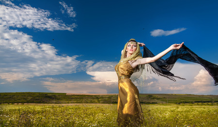 Lovely young lady posing dramatically with long black veil on green field. Blonde woman with cloudy sky in background - outdoor shot. Glamorous female in nature - Arabian style photo
