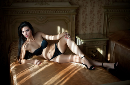 Beautiful sexy brunette young woman wearing black lingerie lying in bed. Fashionable female with attractive body posing provocatively, indoor shot. Sensual girl with high heels shoes on bed in hotel photo
