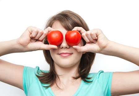 Pretty girl having fun , making glasses with hands and tomatoes photo