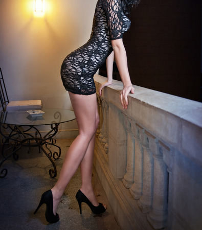 Fashionable perfect body young woman in little black dress posing on a ledge. Side view of sensual female in tight-fit elegant lac Standard-Bild