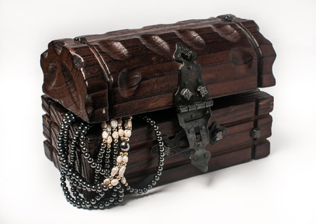 Wooden jewelry box packed with accessories. Wooden treasure trunk with jewelery, isolated on white. Treasure chest with jewelry