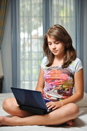 young teen girl laying on her bed in white dress and surfing the internet