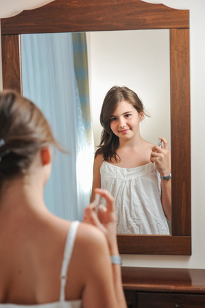 A beautiful teen girl studies her appearance as she looks into the mirror at her beautiful young reflection. Teen girl happy with their appearance in the mirror Stock Photo