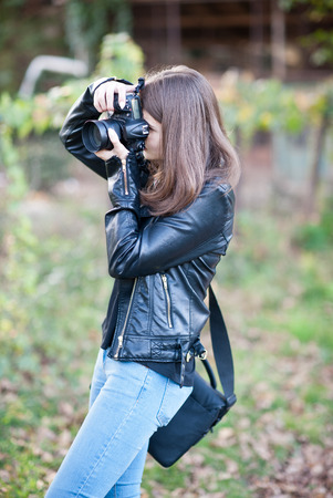 Attractive young girl taking pictures outdoors. Cute teenage girl in blue jeans and black leather jacket taking photos in autumnal park. Outdoor portrait of pretty teen having fun in park with camera Standard-Bild