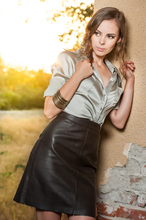 Elegant glamour woman wearing brown skirt and blouse outdoor in the park at sunset Stock Photo