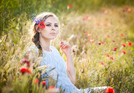 Portrait of beautiful blonde girl with wreath of wild flowers photo
