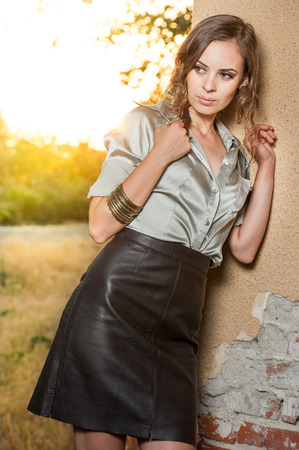 Elegant glamour woman wearing brown skirt and blouse outdoor in the park at sunset. Beautiful woman in skirt and blouse.Slim girl in white blouse relaxing photo