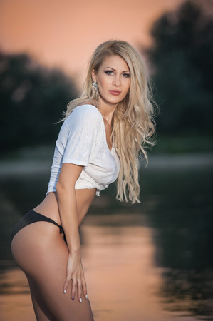 Portrait of young sexy blonde girl in bikini posing provocatively at the beach in sunset. Sensual attractive woman in panties and white T-shirt on beach. Side view of fair hair woman with perfect body Stock Photo