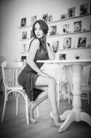 Fashionable attractive young woman in dress sitting in restaurant. Beautiful girl posing in elegant scenery with a juice glass on the table. Pretty female relaxing, indoor shot, black and white photo