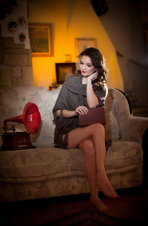 bare feet girl: Beautiful young bare feet woman sitting on sofa holding a book having a red gramophone near her, vintage scenery. Attractive brunette girl with long hair and long legs sitting on couch posing smiling Stock Photo