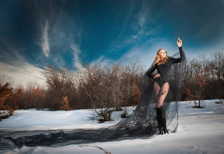 ancient sexy: Lovely young lady posing dramatically with long black veil in winter scenery. Blonde woman with cloudy sky in background - outdoor shoot. Glamorous female in nature - gothic style