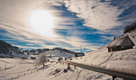Majestic sunset in the mountains landscape. Sunset landscape\ in Carpathian mountains. Dawn in mountains Carpathians, Romania.\ Mountains covered with snow. Mountain road