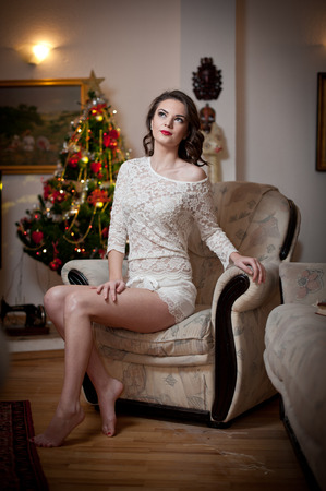 Beautiful sexy woman with Xmas tree in background sitting on elegant chair in cozy scenery. Portrait of girl posing pretty with short dress and bare feet. Attractive brunette female, indoor shot. photo