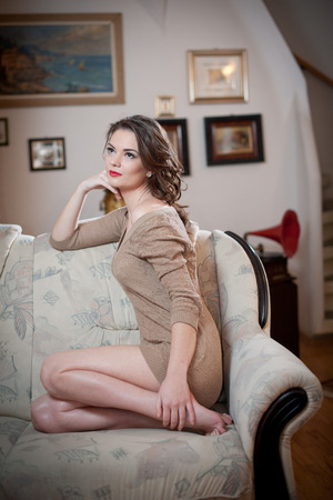 tight fit: Young sensual woman sitting on sofa relaxing. Beautiful long hair girl with comfortable clothes daydreaming on the couch, alone. Attractive brunette wearing a tight fit short dress in cozy scenery Stock Photo