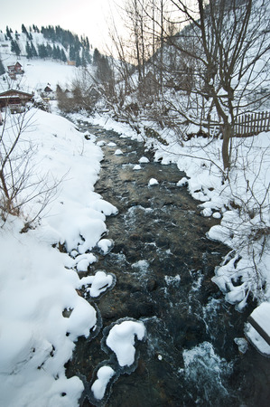 edge of the ice: View of frozen river countryside. Brook in snowy landscape. Romanian small river in winter scenery, Romania, Moeciu. Wild brook in winter season.