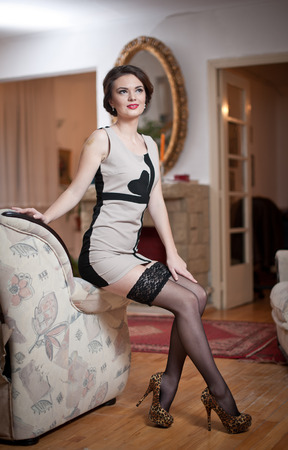 Happy smiling attractive woman wearing an elegant dress and black stockings sitting on the sofa arm.  photo
