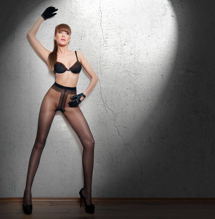 Attractive red hair model with pantyhose and black gloves standing on gray wall. Fashion portrait of sensual long legs woman - indoor shoot. Sensual female in pantyhose posing provocatively.