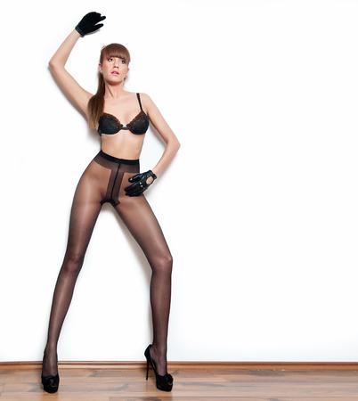 medias veladas: Modelo atractivo de pelo rojo con medias y guantes negros de pie en la pared blanca. Retrato de moda de mujer sensual de piernas largas - en casa y disparar. Hembra sensual en pantimedias posando provocativamente.