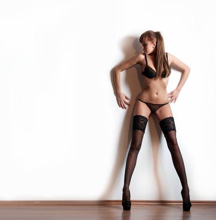 medias veladas: Modelo atractivo de pelo rojo con medias y ropa interior negro de pie en la pared blanca. Retrato de moda de mujer sensual de piernas largas - en casa y disparar. Hembra sensual en pantimedias posando provocativamente.