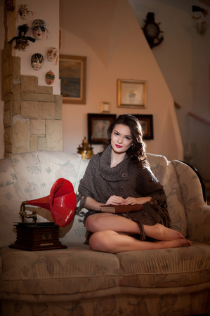 bare feet girl: Beautiful young bare feet woman sitting on sofa holding a book having a red gramophone near her in boudoir scenery. Attractive brunette girl with long hair sitting on couch, vintage scenery Stock Photo