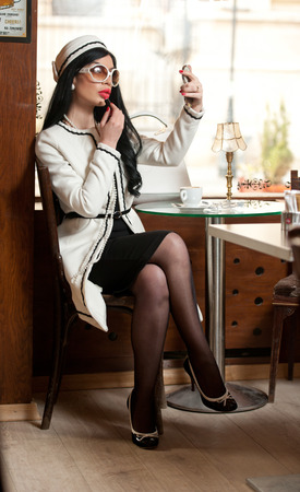 putting lipstick: Fashionable young woman in black and white outfit putting lipstick on her lips and drinking coffee in restaurant. Beautiful brunette in elegant pub with cup of coffee on table looking into the mirror