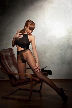 pantimedias: Modelo atractivo pelo rojo con pantimedias negro sienta provocativo en el sillón - fondo gris. Retrato de una sensual mujer - tiro del estudio. Hermosa mujer pelirroja en negro posando provocativamente. Foto de archivo