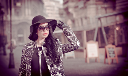 sunglass: Attractive young woman in a winter fashion shot. Beautiful fashionable young girl in black posing on avenue. Elegant brunette with hat, sunglasses and gloves in urban scenery.