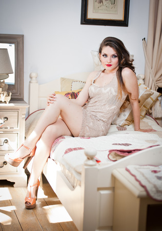 tight dress: Young beautiful sexy woman in white short tight dress posing challenging indoor on vintage bed. Sensual long hair brunette on high heels in bedroom. Attractive female sitting provocatively on bed Stock Photo