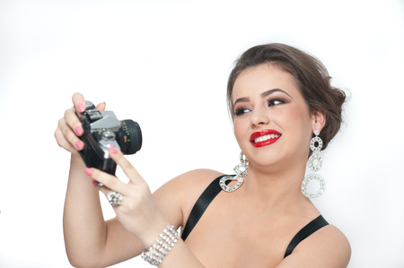 self   portrait: Beautiful young girl with creative make-up and hair style taking photos of herself with a camera. Fashionable attractive woman taking a self portrait. Selfie, indoor, horizontal, over white.