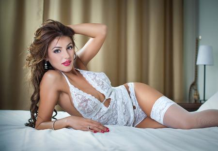 modelos desnudas: Mujer atractiva en ropa interior blanca atractiva que miente en la pose seductora en bed.Brunette con body.portrait sexy de mujer sexy posando en lencer�a blanca en el interior Foto de archivo