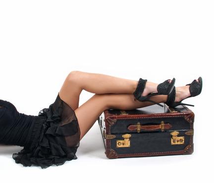 sandalias: Mujer atractiva en vestido negro manteniendo las piernas en una maleta vintage, aislados en fondo blanco, tiro del estudio. Vista lateral de la mujer perfecta del cuerpo con las piernas largas hermosas en los altos talones