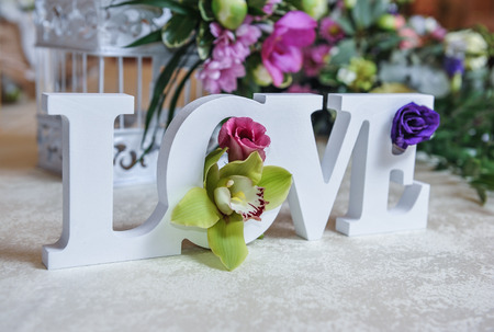 Wedding decor LOVE letters and flowers on table. Fresh flowers and LOVE decoration on festive table. Luxurious wedding decoration on restaurant table. Elegant event