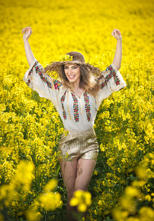 Young girl wearing Romanian traditional blouse posing in canola field with cloudy sky in background outdoor shot. Portrait of beautiful blonde with straw hat smiling in rapeseed field