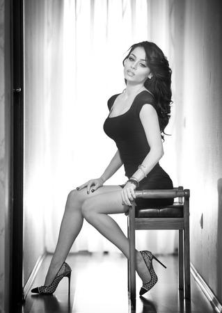 Attractive sexy brunette with long legs sitting on a chair with daylight in background. Portrait of sensual woman wearing a short black dress an high heels shoes black and white photo