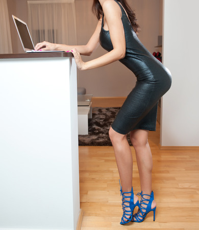 Perfect body woman in short tight fit leather dress working on the laptop in living room. Side view of sensual young female with long legs and high heels standing in front of computer