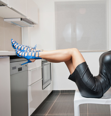 Perfect body woman in short tight fit leather dress and blue shoes posing relaxed in a modern kitchen. Side view of sensual young female with long legs on high heels sitting on a chair indoor