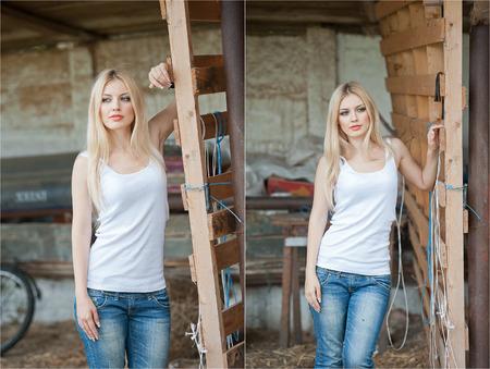 plan �loign�: Plan d'une belle jeune fille pr�s d'une vieille cl�ture en bois. �l�gant usure de look: top blanc de base, jeans en denim. Agriculteur de style Country. Belle blonde les cheveux longs dans un style rustique Banque d'images