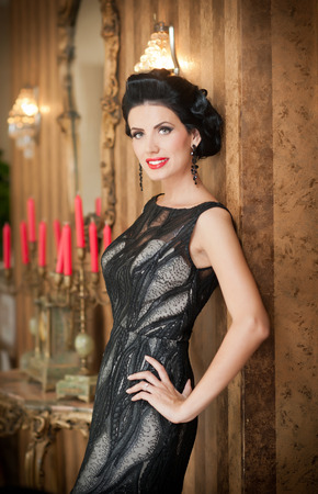 retro lady: Beautiful girl in elegant black dress posing in vintage scene. Young beautiful woman wearing luxurious dress. Seductive brunette woman in luxury manor. Gorgeous lady with creative haircut smiling