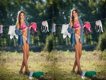 Sexy brunette woman in bikini and shirt putting clothes to dry in sun. Sensual young female with long legs putting out the washing to dry in sunny day. Perfect body housewife, outdoor shot in forest