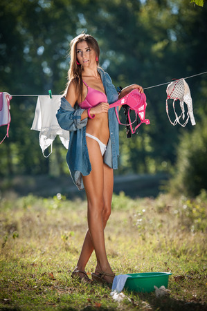 sexy housewife: Sexy brunette woman in bikini and shirt putting clothes to dry in sun. Sensual young female with long legs putting out the washing to dry in sunny day. Perfect body housewife, outdoor shot in forest