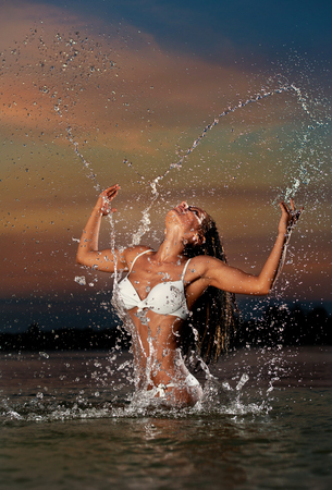 erotic women: Sexy brunette woman in wet white swimsuit posing in river water with sunset sky on background. Young female playing with water in twilight scenery. Attractive girl in summer evening over dramatic sky.