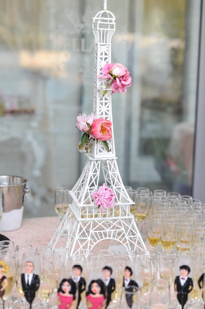 la tour eiffel: Wedding decoration with pink roses on Eiffel tower miniature. Elegant and luxurious event arrangement with La tour Eiffel and nice glasses painted as people around. French decoration for fancy event