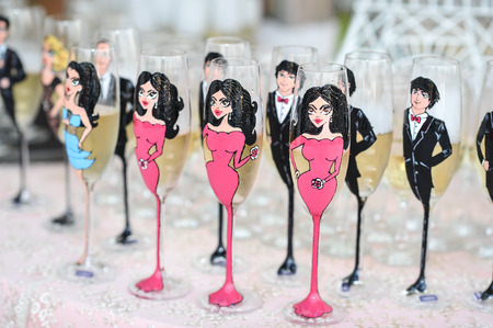 wedding table decor: Wedding decor, wine glasses and champagne flutes on table. Champagne flutes painted as women and men. Festive wedding glasses with decor