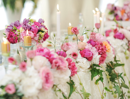 decoration: Wedding decoration on table. Floral arrangements and decoration. Arrangement of pink and white flowers in restaurant for luxury wedding event Stock Photo