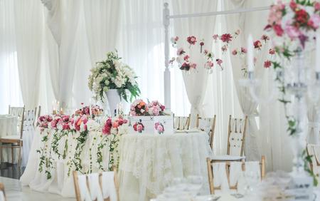 Decoración de la boda en la mesa. Arreglos y decoración floral. Arreglo de flores de color rosa y blanco en el restaurante para eventos de la boda de lujo Foto de archivo