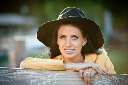 american falls: Beautiful brunette girl with country look near an old wooden fence. Attractive woman with black hat and yellow coat,  American country style farmer. Long hair dark hair female in rustic style