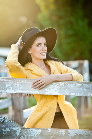sexy cowboy: Beautiful brunette girl with country look near an old wooden fence. Attractive woman with black hat and yellow coat,  American country style farmer. Long hair dark hair female in rustic style