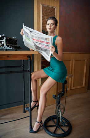 Fashionable attractive young woman in short tight fit green dress sitting in restaurant on high chair reading newspapers. Beautiful long legs brunette posing indoors. Pretty female reading in pub.