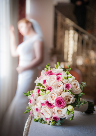 Bride in window frame and wedding bouquet in the foreground. Wedding bouquet with a woman in wedding dress in the background. Beautiful bouquet of white and pink rose flowers. Elegant wedding bouquet