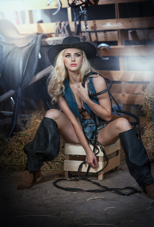 Beautiful blonde girl with country look, indoors shot in stable, rustic style. Attractive woman with black cowboy hat and denim shorts, American country style farmer with barn harness in background